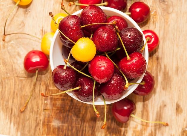물 방울, 필드의 작은 깊이로 덮여 근접 잘 익은 빨간 체리, 열매는 흰색 그릇에 나무 테이블에 있습니다