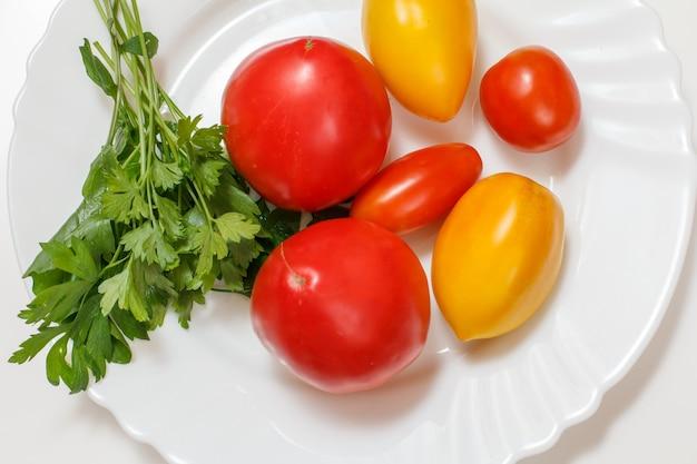 Спелые помидоры крупным планом и листья петрушки на белой фарфоровой тарелке. ингредиенты для вегетарианской пищи. вид сверху.
