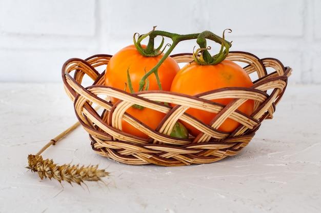 白い織り目加工の表面に籐のバスケットと小麦の穂を持つクローズアップ熟した黄色のトマト