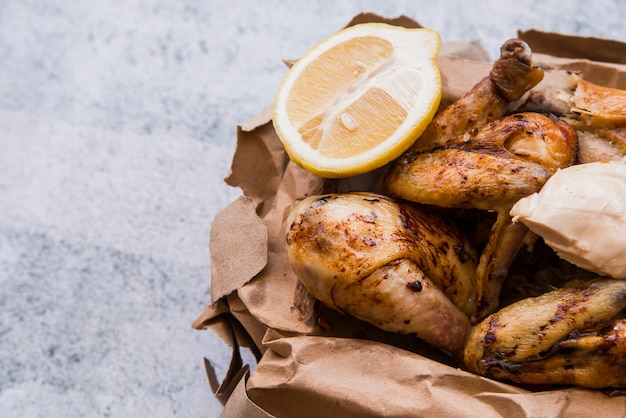 Close-up of roasted chicken and lemon slice in brown paper