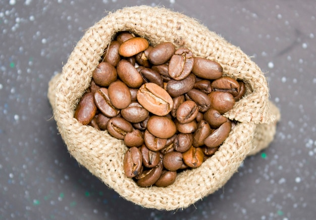 Close-up of roasted coffee beans in a burlap bag on a dark background, top view