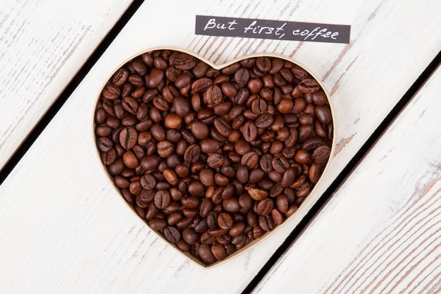 Close up roasted coffee beans forming heart form. but first coffee. top view flat lay.