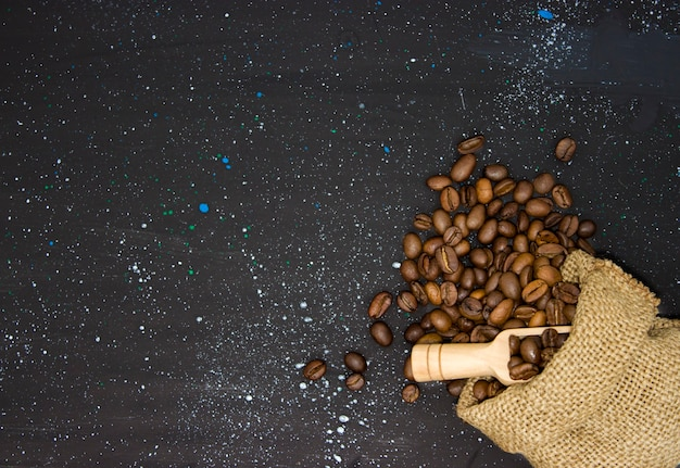 Close - up of roasted coffee beans poured into a bag of burlap on a dark background, top view. wooden shovel next to the bag