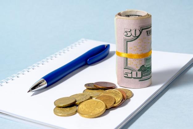 근접 압연 미국 달러 지폐와 동전 메모장에 누워