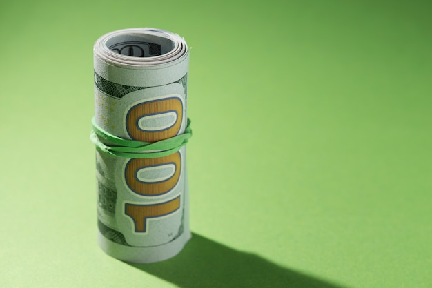 Close-up of rolled up banknotes on green background