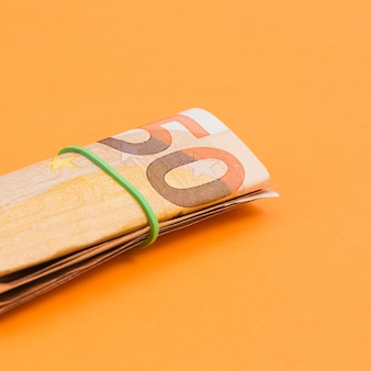 Close-up of rolled up euro note tied with rubber on an orange backdrop