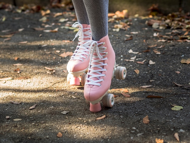Close-up of roller skates with legs in socks