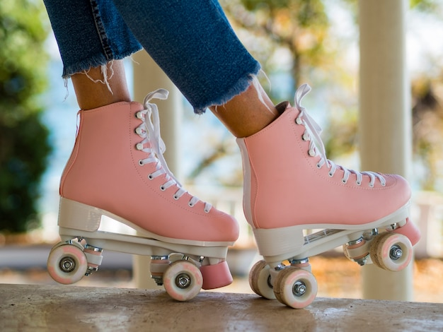 Close-up of roller skates with woman in jeans