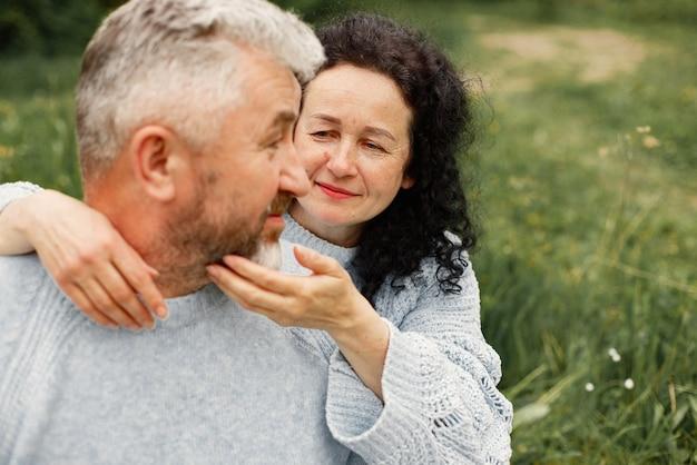 Primo piano coppia romantica seduta nel parco autunnale e abbracciata di giorno