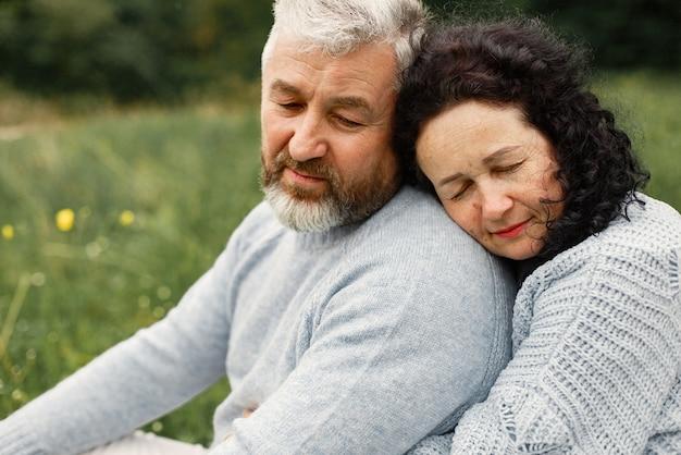 秋の公園に座っているロマンチックなカップルをクローズアップ