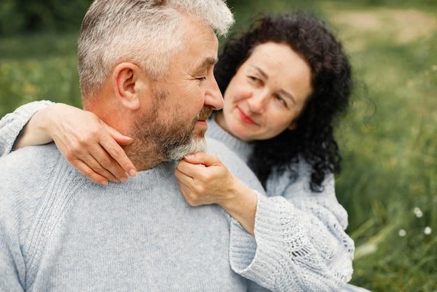 秋の公園に座って、昼間に抱き締めるロマンチックなカップルをクローズアップ