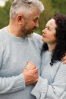 Coppia romantica ravvicinata in piedi nel parco autunnale e abbracciata di giorno