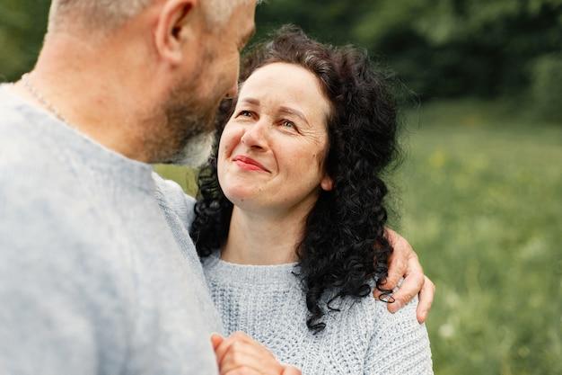 秋の公園に立って、昼間に抱き締めるロマンチックなカップルをクローズアップ