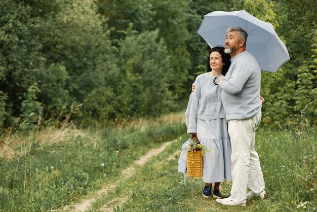昼間に傘の下で秋の公園に立っているロマンチックなカップルをクローズアップ