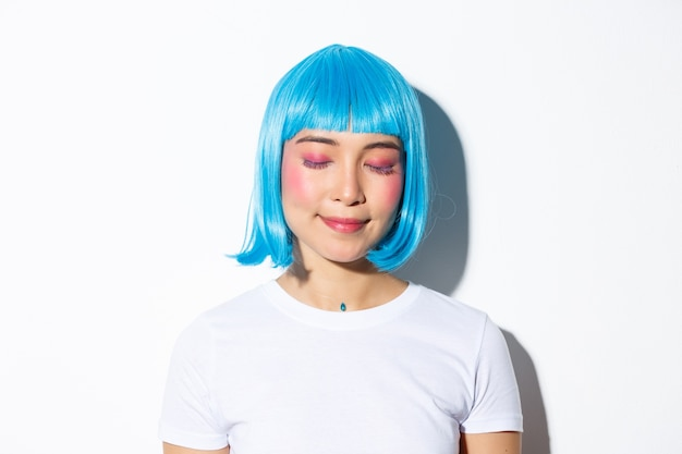 Close-up of romantic, cute asian woman in blue wig, close eyes and daydreaming with pleased smile, standing.