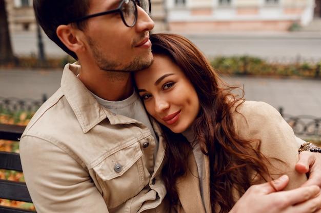 Закройте вверх по романтичному портрету молодой красивой пары в влюбленности обнимая на стенде в парке осени. ношение стильного бежевого пальто.