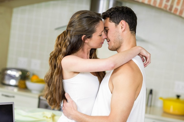 Close-up of romantic young couple cuddling in kitchen