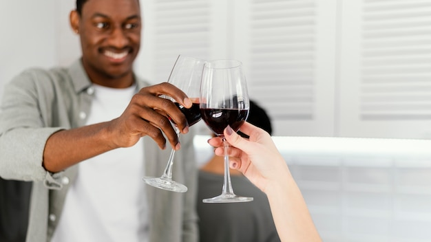 Close up roommates clinking glasses of wine