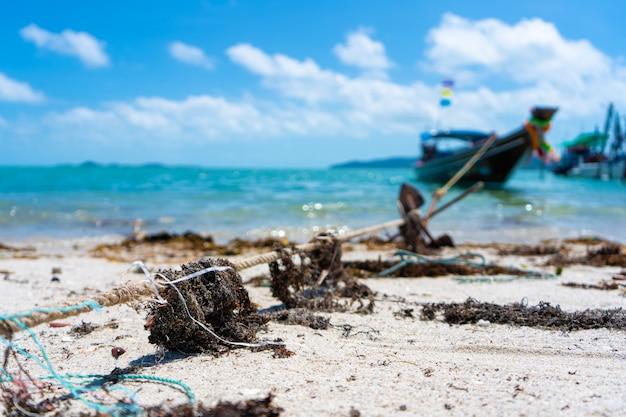 Макро веревка для швартовки лодки на пляже, в сухих морских водорослей.