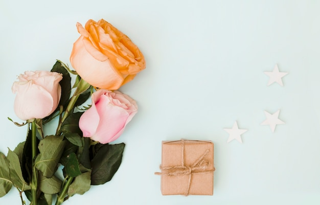 Close-up of roses; gift box and cut out three stars on colored background