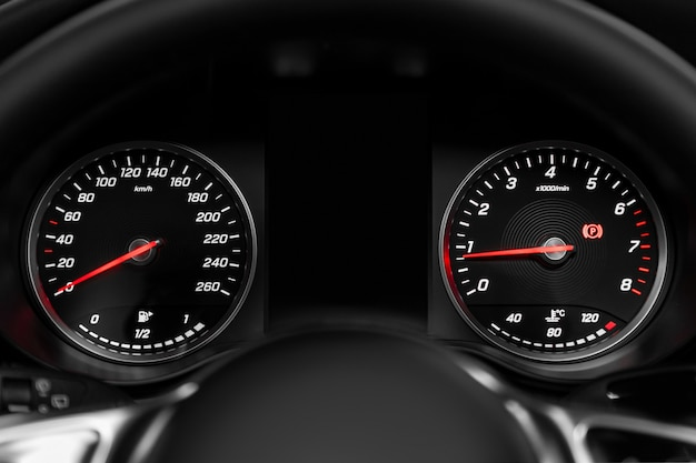 Close-up of round dashboard, speedometer and tachometer with white backlight. modern car interior