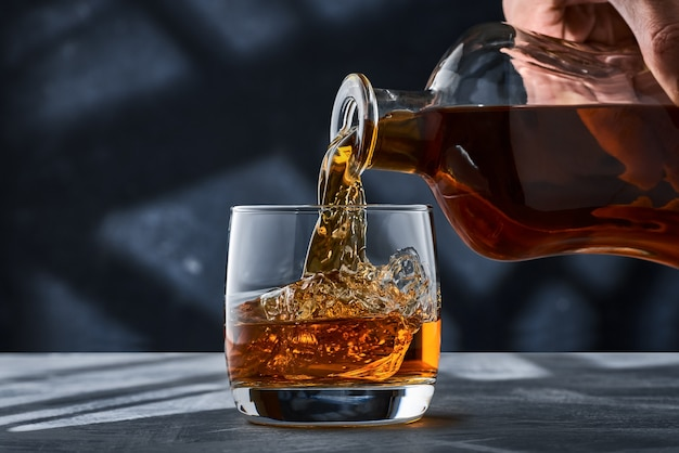 Close up of a round glass of whiskey with ice on the table