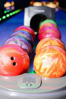 Close up of row of bowling balls in hall. bowling bowls return system