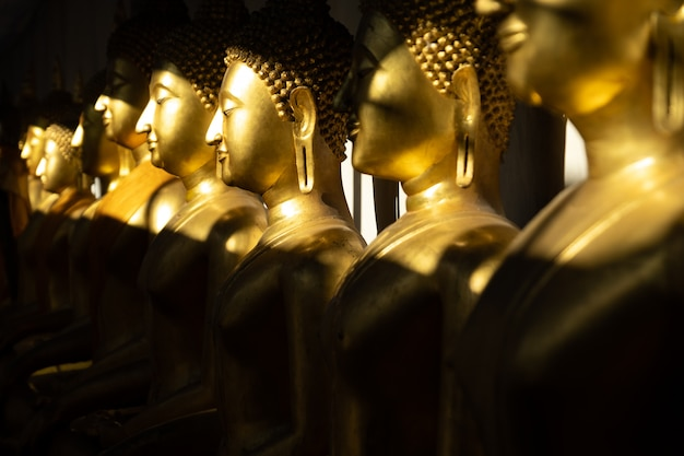 Close up row of golden buddha statue in the light and shadow of sun at wat pra sri mahathat temple