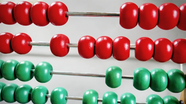 Close-up rows of red and green wooden beads of abacus