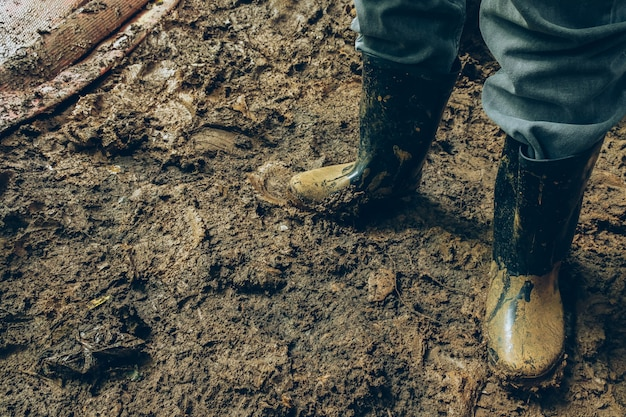 ゴム雨の靴を泥の作業oの汚れた場所で閉じてください。