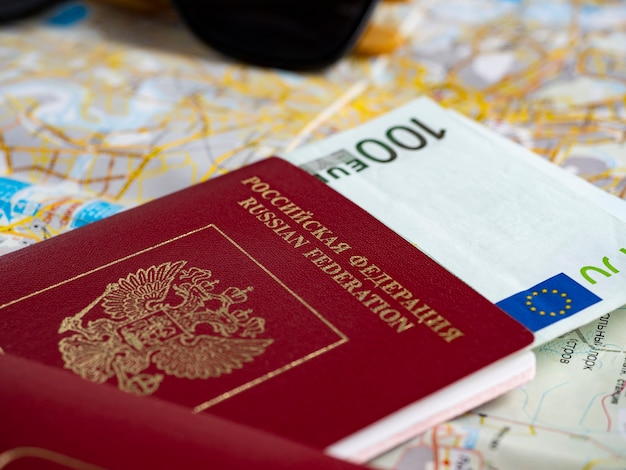 A close-up of a russian passport with embedded euro bills is on the map. the concept of travel and recreation