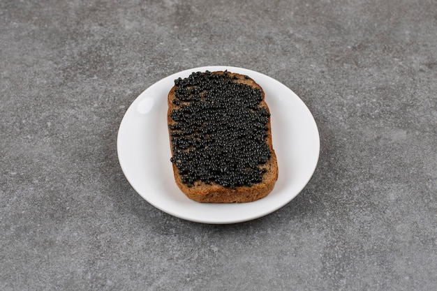 Close up of rye bread with black caviar on white bread