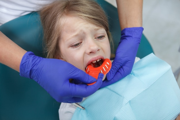 Close up of a sad little girl crying during dental treatment