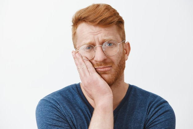 Close-up of sad unhappy redhead man looking gloomy, express regret