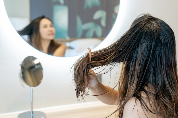 Close up of sad young woman using wooden comb brush her damaged and tangled wet hair in front of mirror