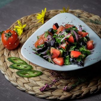 Insalata di primo piano con pomodoro, cetriolo, lattuga, cipolle, basilico, olive in un piatto bianco su un supporto di vimini