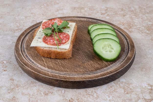 Primo piano di panino al salame con fette di cetriolo