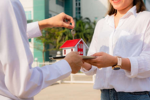 Close up salesman holding home key to customer