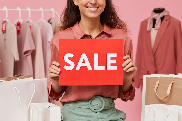 Close-up of saleswoman holding sale placard and smiling while working in the shop