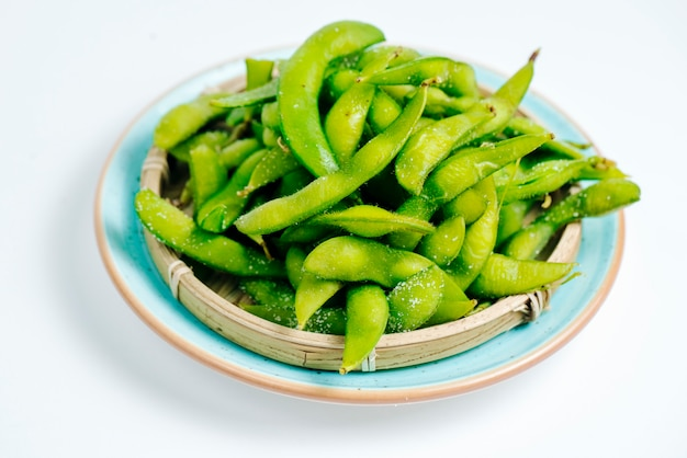Close up of salted edamame plate in white background