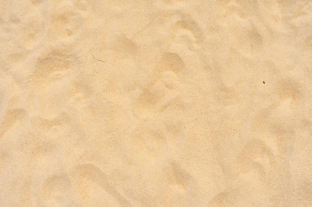 배경으로 여름 햇볕에 해변에서 모래 질감을 닫습니다
