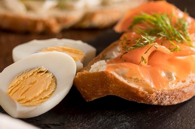 Primo piano del panino sull'ardesia con il salmone e l'uovo sodo