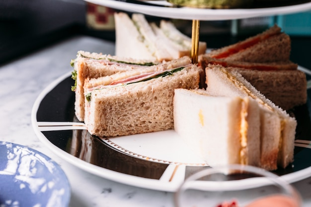 Close up sandwiches on 3 tier ceramic serving tray for eating with hot tea.