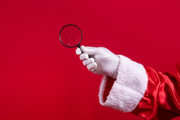 Close-up of santa's gloved hand holding a magnifying glass.