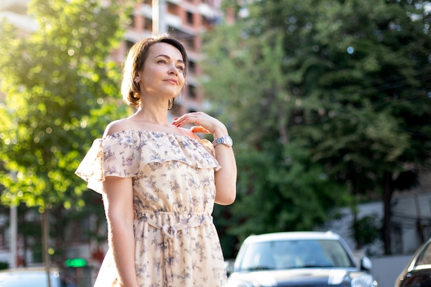 Close-up of a satisfied adult woman in a dress walks along an urban street and looks ahead. femininity and beauty concept. world tourism day