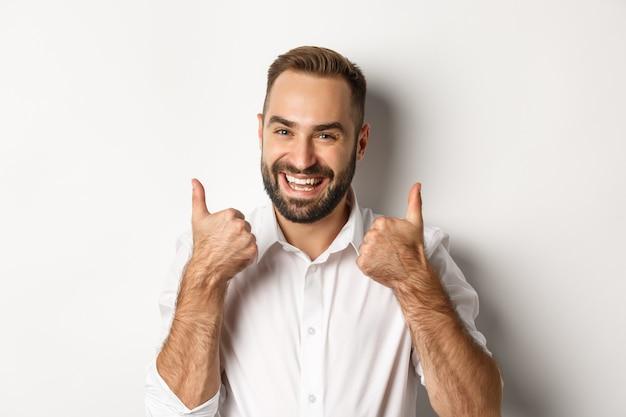 Primo piano del ragazzo barbuto soddisfatto in camicia bianca, che mostra i pollici in su in approvazione, come e d'accordo, risposta positiva