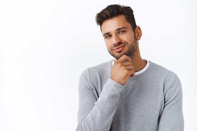 수염이 난 잘생긴 남자는 좋은 결정에 대해 자랑스럽거나 만족스러운 선택을 하고, 승인에 미소를 짓고 턱을 문지르고, 동의하는 표정을 짓고, b-day 선물로 여자친구를 사주는 것과 같은 생각을 했습니다.