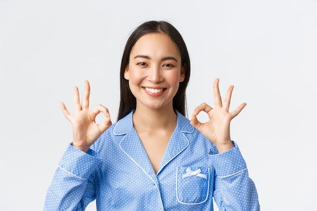 Primo piano di una donna asiatica felice soddisfatta in pigiama blu valuta un buon lavoro, consiglia una qualità perfetta del prodotto o del servizio, garantisce qualcosa come mostra gesto ok compiaciuto, sfondo bianco