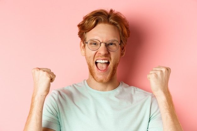 Close up of satisfied lucky redhead man winning, shouting from joy and making fist pump, celebratig victory, standing like champion over pink background.