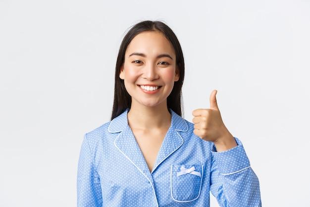 Primo piano di donna asiatica abbastanza sorridente soddisfatta in pigiama blu che mostra il pollice in su in segno di approvazione, raccomanda e garantisce la qualità del prodotto, in piedi soddisfatto su sfondo bianco